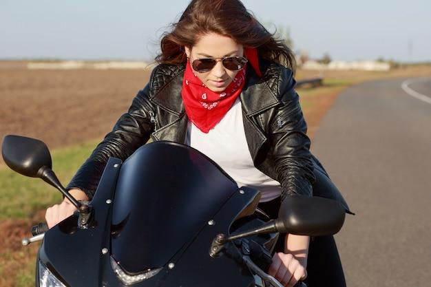 Bella giovane donna in elegante giacca di pelle nera, bandana rossa e occhiali da sole, in sella a una moto, posa su strada