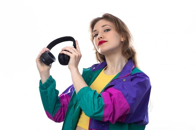 Bella giovane donna in giacca colorata e tenendo le cuffie