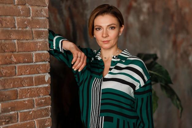 Bella giovane donna in giacca verde in posa sul muro di mattoni.