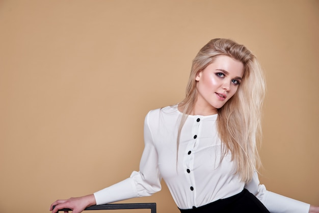 Bella giovane donna in gonna nera e camicia bianca ritratto. ragazza graziosa felice, bionda, parete marrone