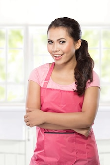 Bella giovane donna in grembiule rosa