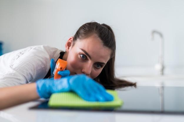 Bella giovane donna in guanti protettivi che pulisce forno con lo straccio