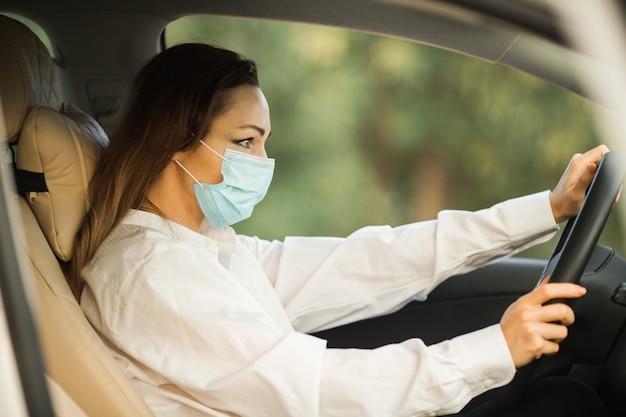 Bella giovane donna in mascherina medica alla guida di un'auto