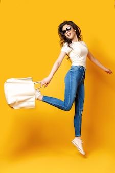 Bella giovane donna in occhiali da sole, camicia bianca, blue jeans che salta con la borsa su sfondo giallo