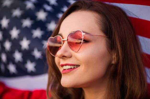 Bella giovane donna in occhiali da sole rosa con bandiera americana