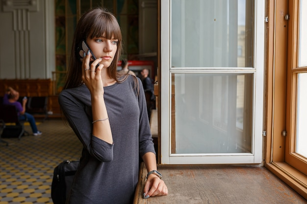 Bella giovane donna in piedi alla finestra con il telefono