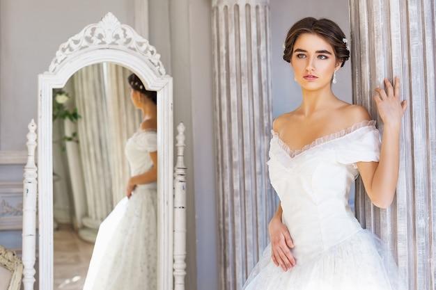 Bella giovane donna in piedi in abito bianco vicino allo specchio.