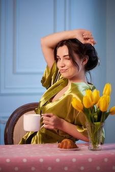 Bella giovane donna in pigiama bere caffè al mattino con croissant.