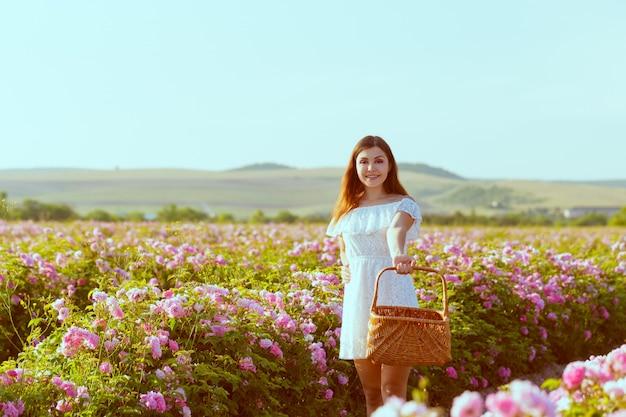 Bella giovane donna in posa vicino a rose in un giardino.