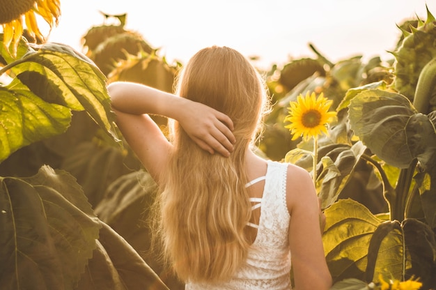 Bella giovane donna in un campo di girasoli. ritratto di una giovane donna al sole. concetto di allergie ai pollini