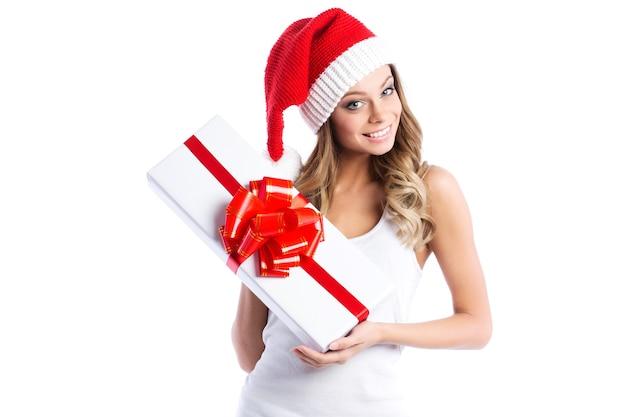 Bella giovane donna in un cappello da babbo natale che tiene in mano una confezione regalo bianca con nastro rosso isolato.