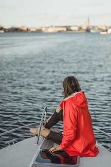 Bella giovane donna in un impermeabile rosso cavalca uno yacht privato. stoccolma, svezia