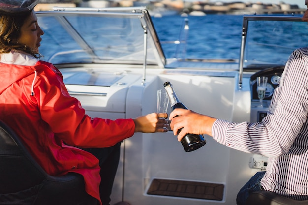 Bella giovane donna in un mantello rosso che beve champagne su uno yacht.