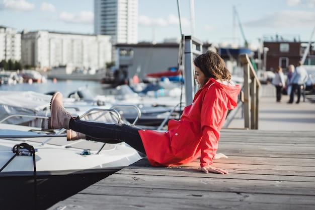 Bella giovane donna in un mantello rosso nel porto degli yacht. stoccolma, svezia