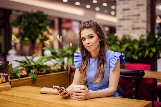 Bella giovane donna in un vestito blu in città