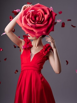 Bella giovane donna in un vestito lussuoso con rose, petali di rosa, immagine elegante, rossetto rosso