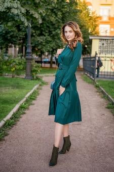 Bella giovane donna in una passeggiata in un abito verde.