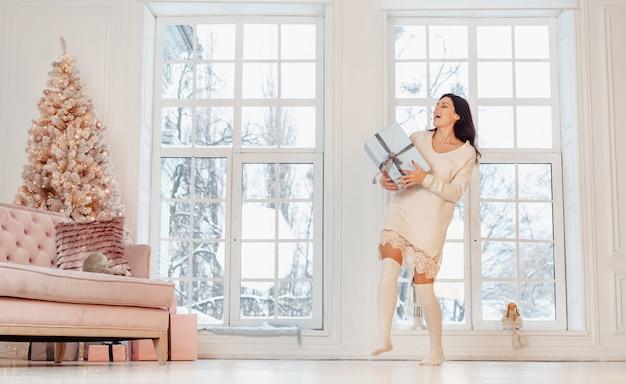 Bella giovane donna in vestito bianco che posa con il contenitore di regalo