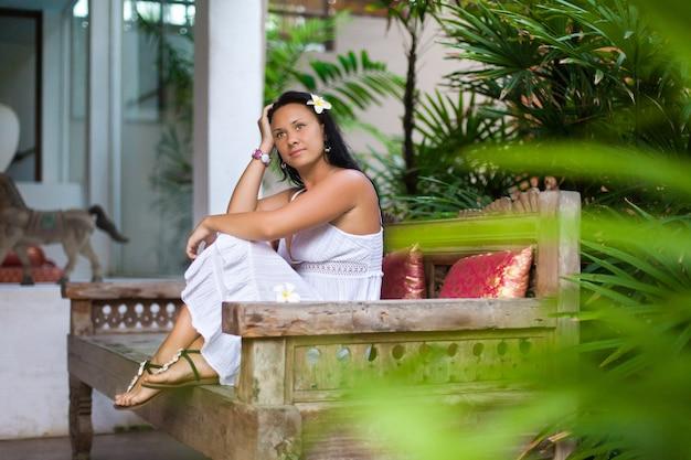 Bella giovane donna in vestito bianco che riposa sul sofà d'annata in giardino.