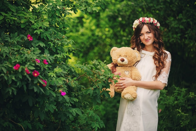 Bella giovane donna incinta che porta vestito bianco e corona floreale e che tiene orsacchiotto nel parco di verde di estate, estate, ragazza incinta. il concetto di maternità