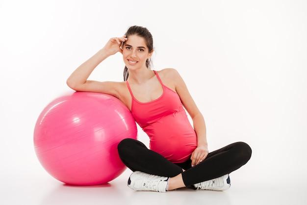 Bella giovane donna incinta che si siede con fitball
