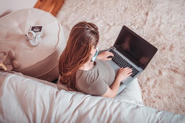 Bella giovane donna incinta che si siede sul letto nella maschera facendo uso dei dispositivi di tecnologia. mamma futura che aspetta bambino che si rilassa con il computer all'interno. fermare la quarantena coronavirus o covid-19 ncov.