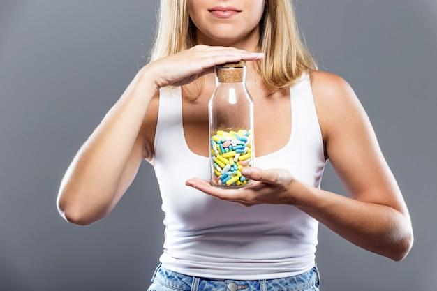 Bella giovane donna mostrando bottiglia di pillole su sfondo grigio.