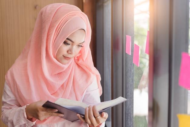 Bella giovane donna musulmana che legge un libro davanti all'ufficio della parete di vetro.