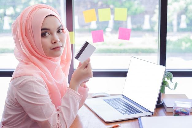 Bella giovane donna musulmana che mostra una carta di credito con il computer portatile nell'ufficio. laptop schermo vuoto