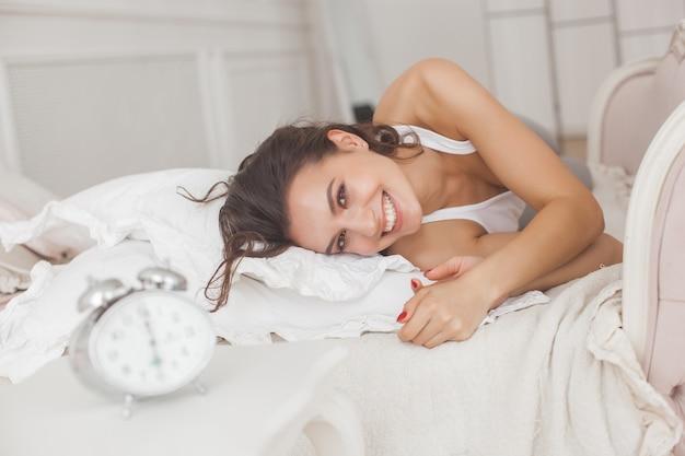 Bella giovane donna nel letto di mattina