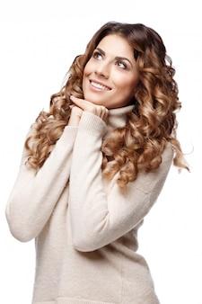 Bella giovane donna nel sorridere tricottato del maglione della lana
