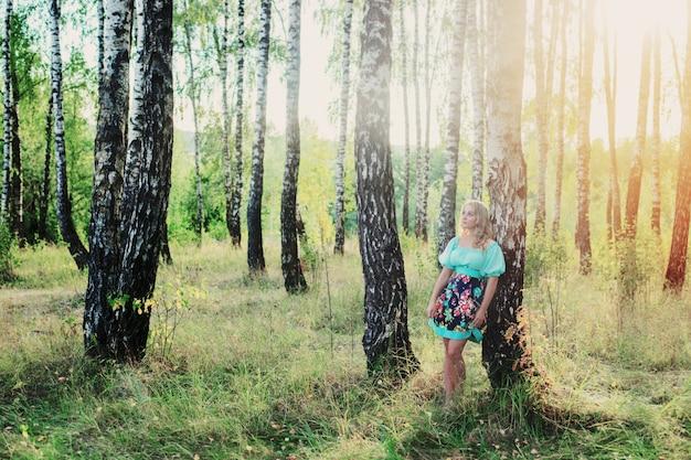 Bella giovane donna nella foresta di betulle