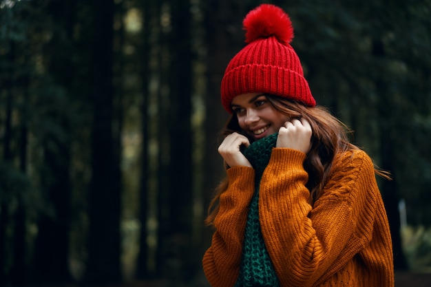 Bella giovane donna nella foresta in abiti luminosi, un cappello rosso, un maglione arancione, in una sciarpa verde viaggia, escursioni nella natura nella foresta