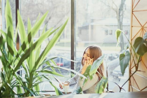Bella giovane donna parla al cellulare e sorridente in un caffè