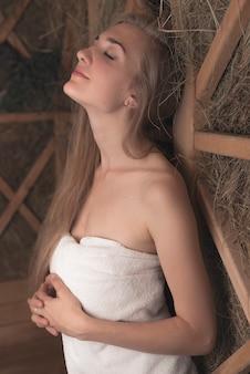 Bella giovane donna rilassata che si appoggia sulla parete di legno