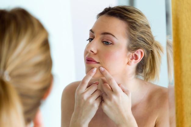 Bella giovane donna rimuovendo brufolo dal suo viso in una casa di bagno.