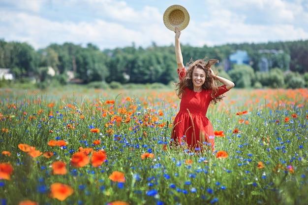 Bella giovane donna romantica in cappello di paglia sul campo di fiori di papavero