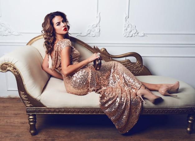 Bella giovane donna sbalorditiva in un fantastico vestito di glitter e paillettes, seduta sul divano di lusso