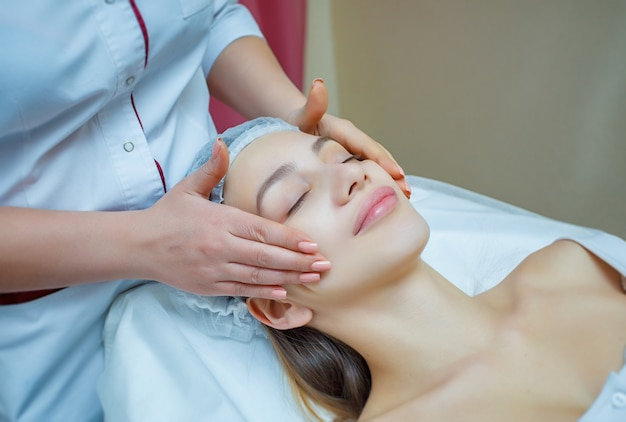 Bella giovane donna sdraiata con gli occhi chiusi e con massaggio viso e testa presso spa