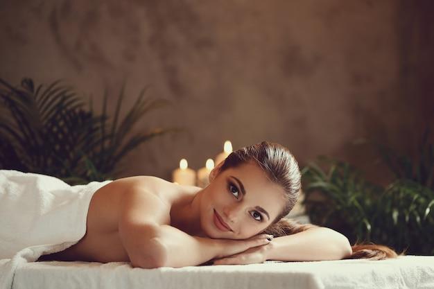 Bella giovane donna sdraiata e in attesa del suo massaggio. concetto di spa