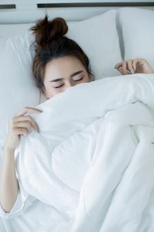 Bella giovane donna sdraiata nel letto e dormire.