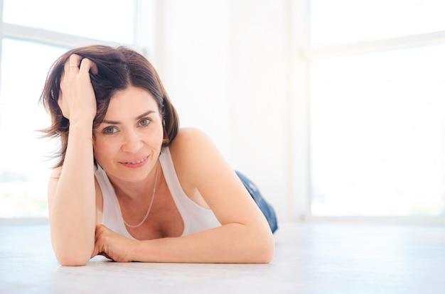 Bella giovane donna sdraiata su un pavimento