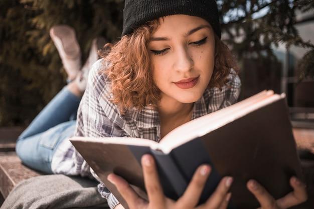 Bella giovane donna sdraiata sulla panchina e leggendo il libro