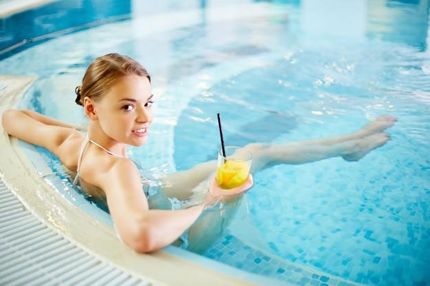 Bella giovane donna seduta con il cocktail in vasca idromassaggio