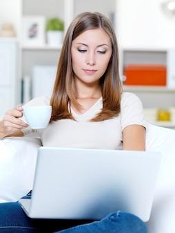 Bella giovane donna seria con il computer portatile e la tazza di caffè sul divano