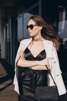 Bella giovane donna sexy in occhiali da sole, ragazza glamour nella giacca bianca elegante