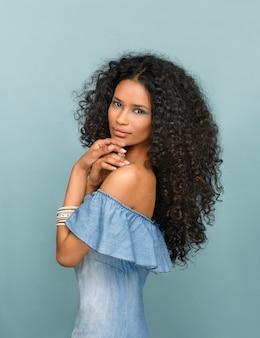 Bella giovane donna snella alla moda da santo domingo con lunghi capelli neri ricci sul blu