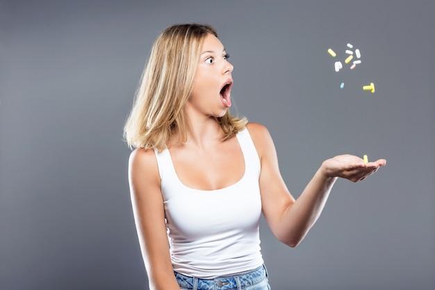 Bella giovane donna sorpresa gettando pillole su sfondo grigio.