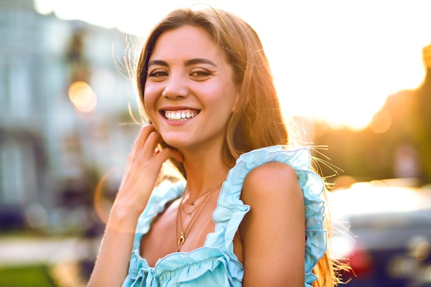 Bella giovane donna sorridente beata che posa in strada, luce solare intensa, vestito blu elegante alla moda, trucco naturale e umore positivo.