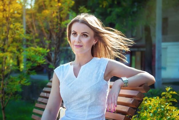 Bella giovane donna sorridente, che indossa un elegante abito bianco, seduto sulla panchina in un parco con i capelli che volano nel vento alla luce del tramonto estivo